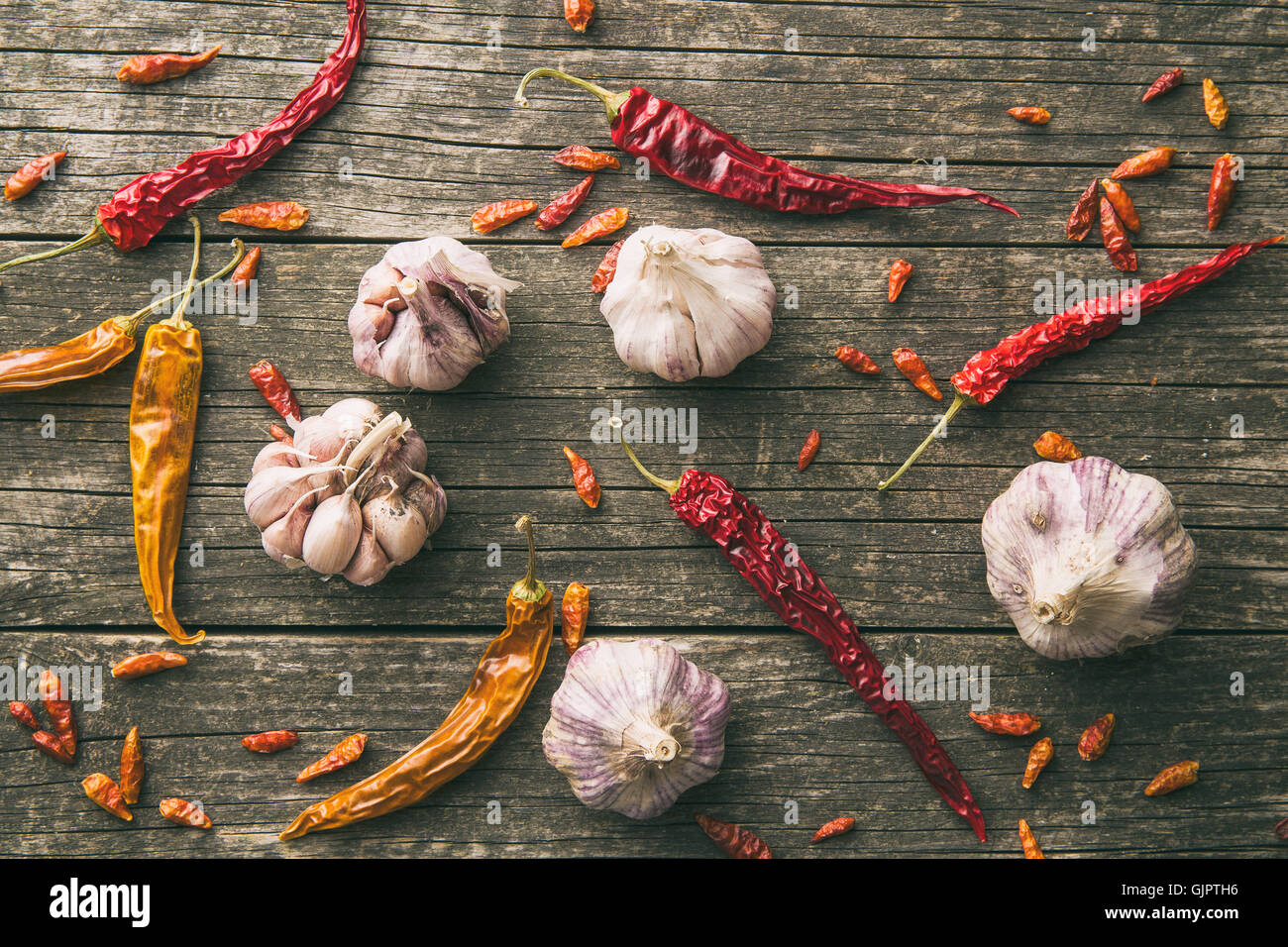 Garlic and chili peppers on old wooden table. Top view. - Stock Image