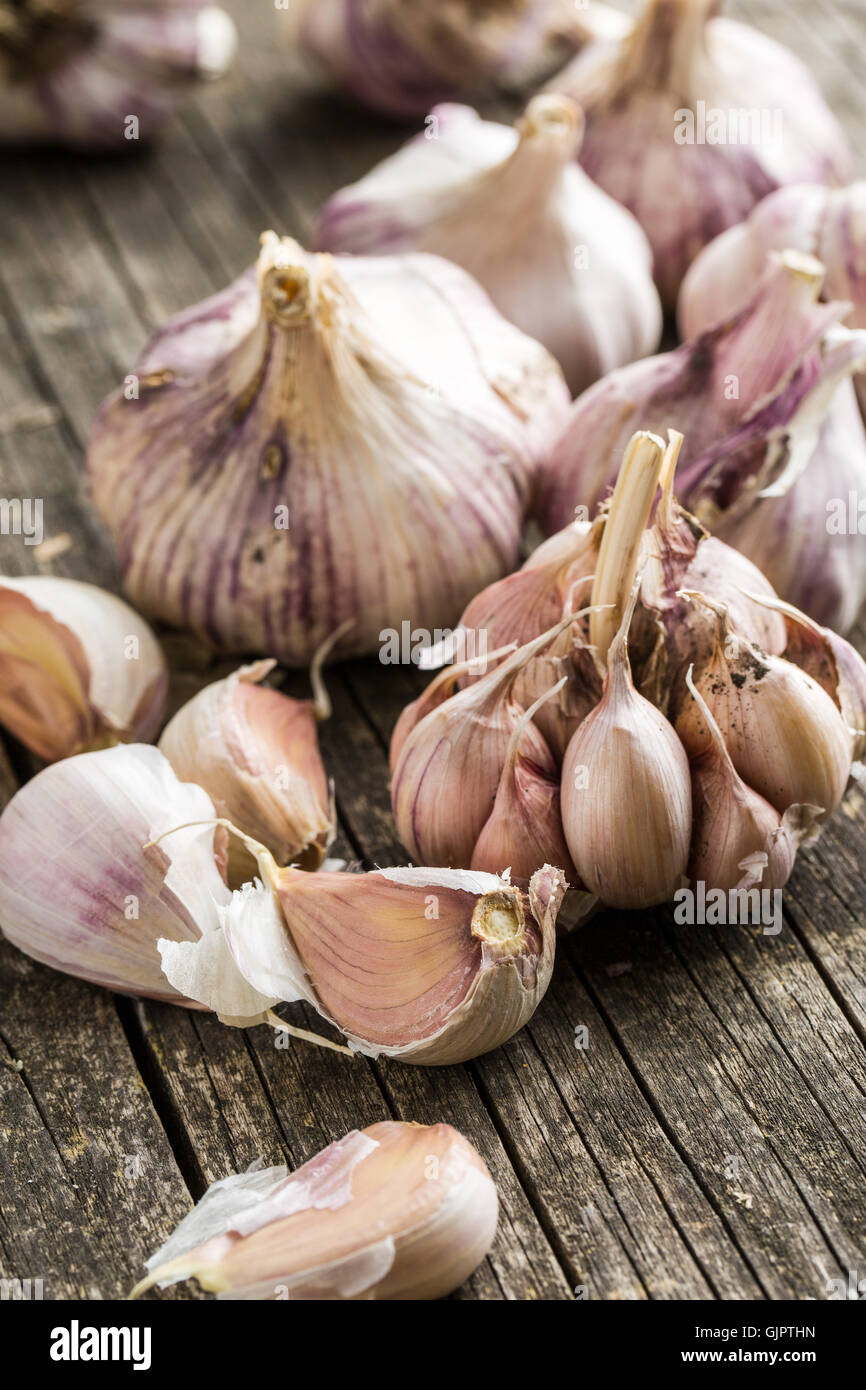 Tasty garlic on old wooden table. - Stock Image