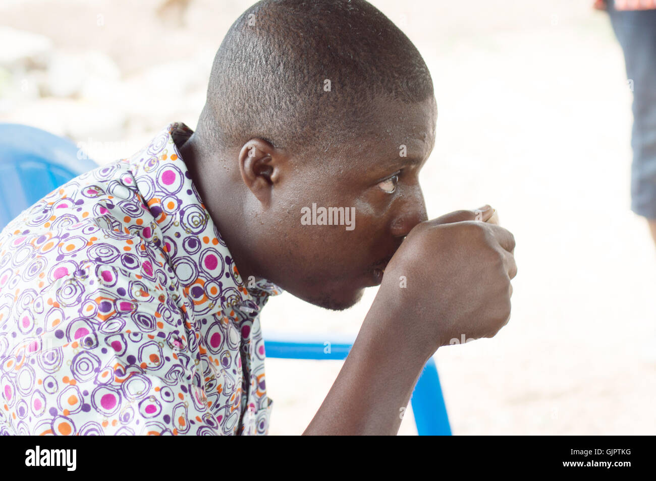 with a traditional cup in hand , this young man refreshes the throat by the palm wine. - Stock Image
