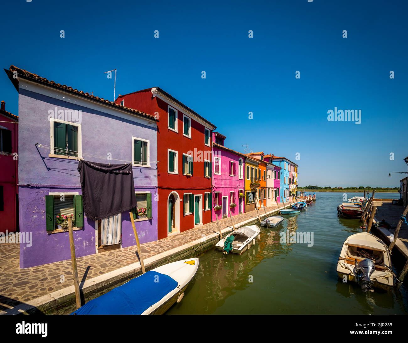 The traditional colourful painted buildings with laundry hanging outside on washing-lines, on the island of Burano. - Stock Image