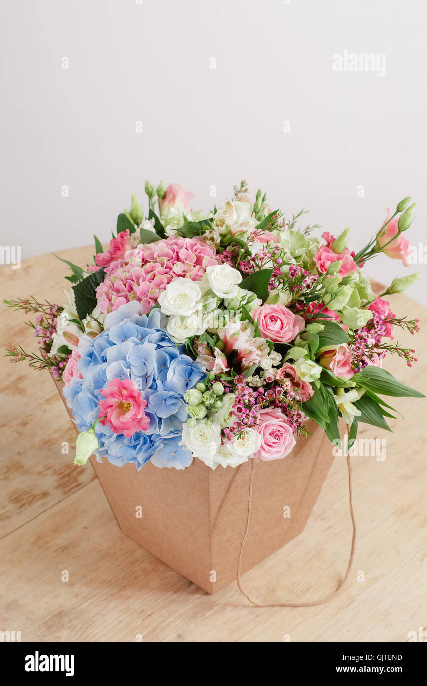 hydrangea rich bouquet. Vintage floristic background, colorful roses, in crafting the package on the wooden table - Stock Image