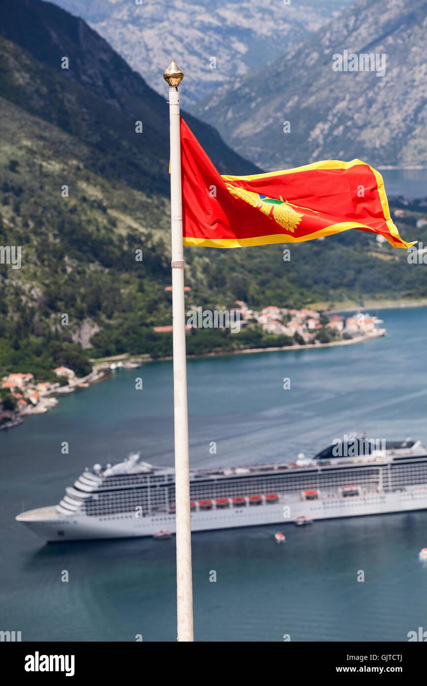 Montenegrin national flag on background of cruiseferry in Gulf of Kotor (Boka Kotorska), Montenegro Stock Photo