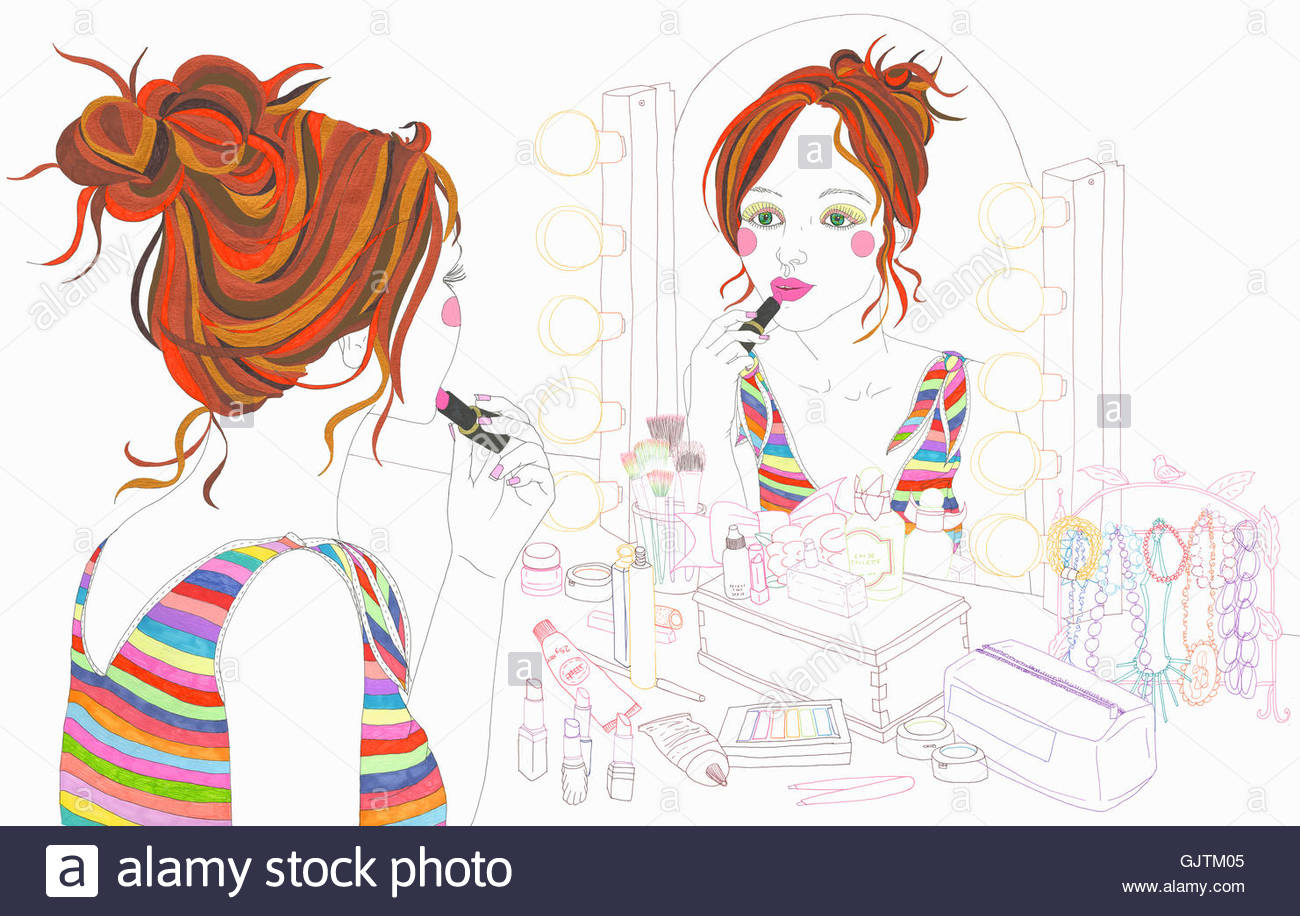 Young woman applying lipstick looking in dressing table mirror - Stock Image