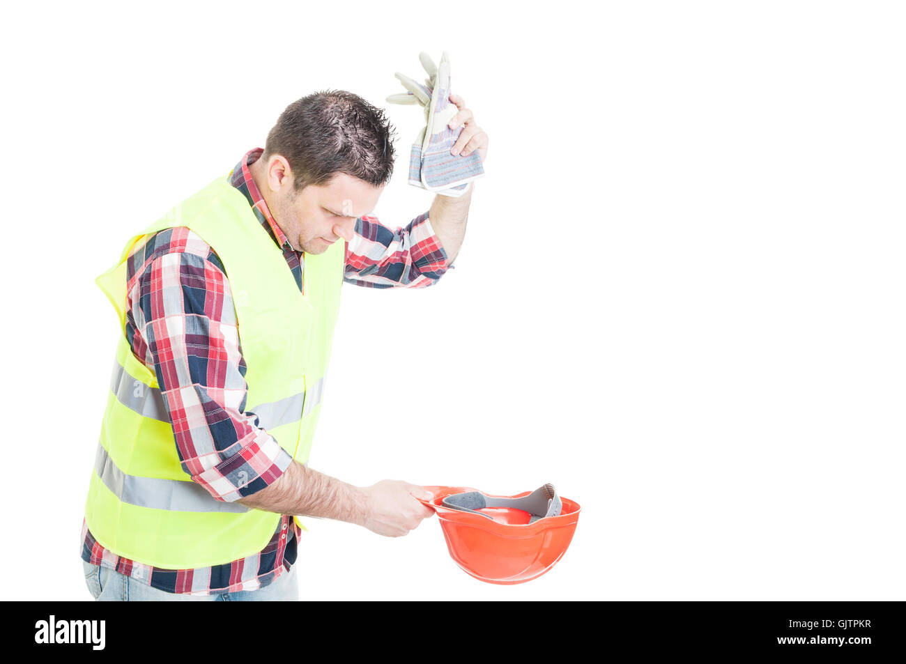 Angry builder throwing his gloves into helmet as frustration concept isolated on white background with copyspace - Stock Image