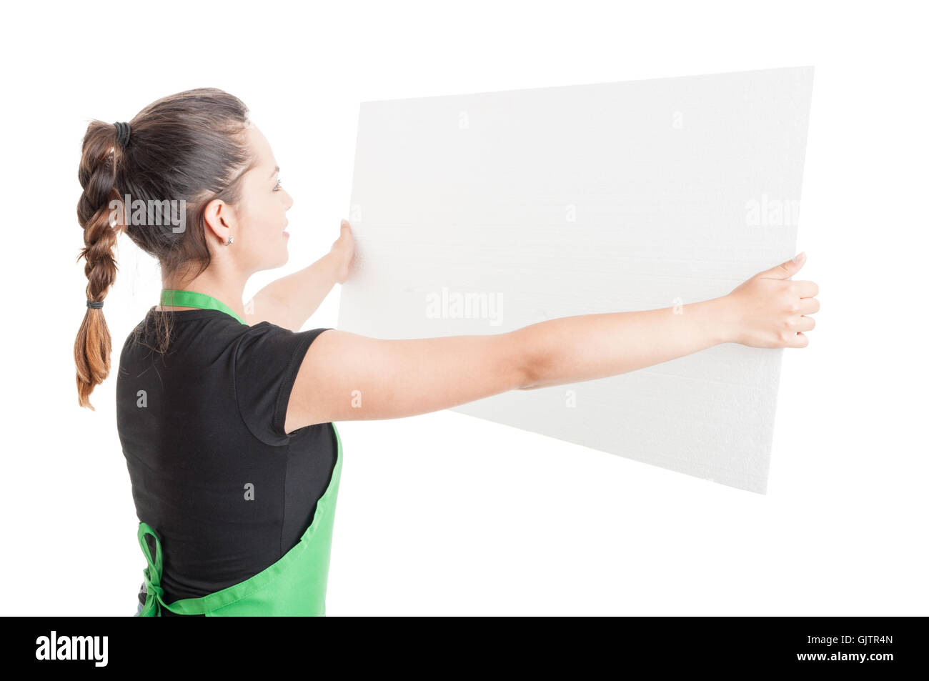 Young saleswoman holding big empty billboard with copy space or text area isolated on white background - Stock Image