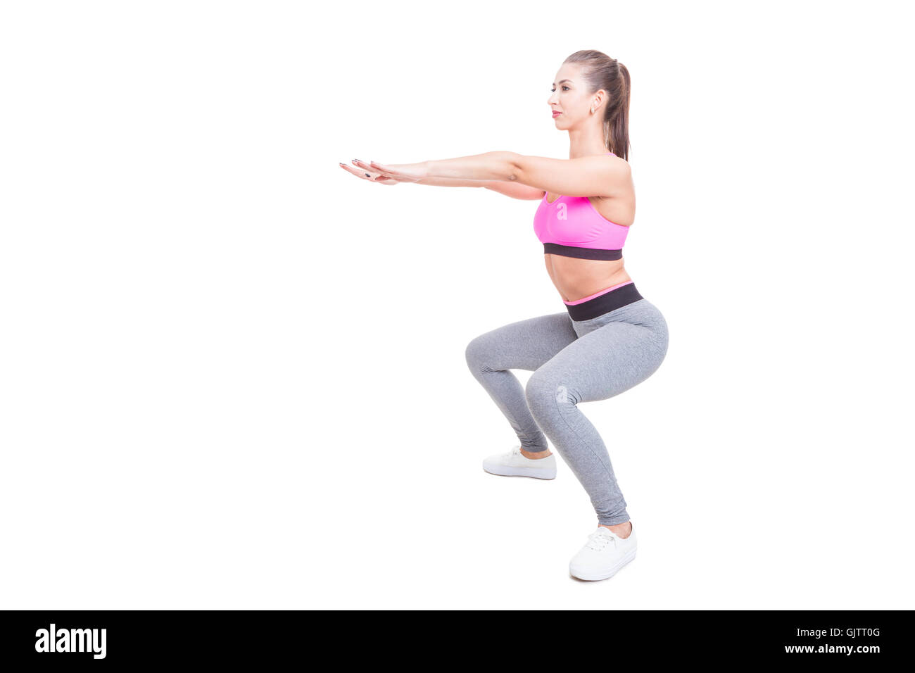 Fit girl working out doing squats with hands up isolated on white background with copy text space - Stock Image