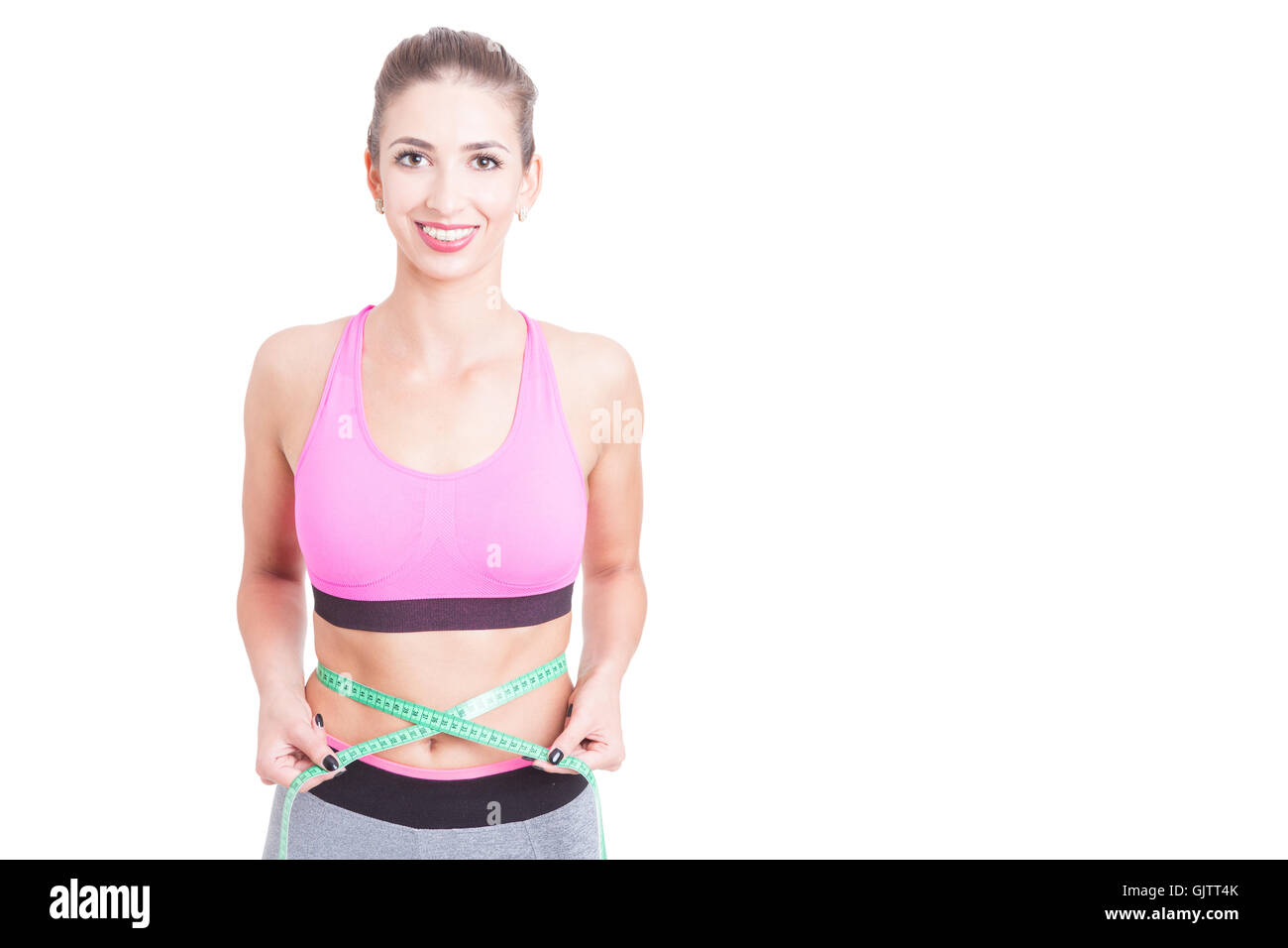 Girl at gym holding centimeter around waist isolated on white background with copy text space - Stock Image