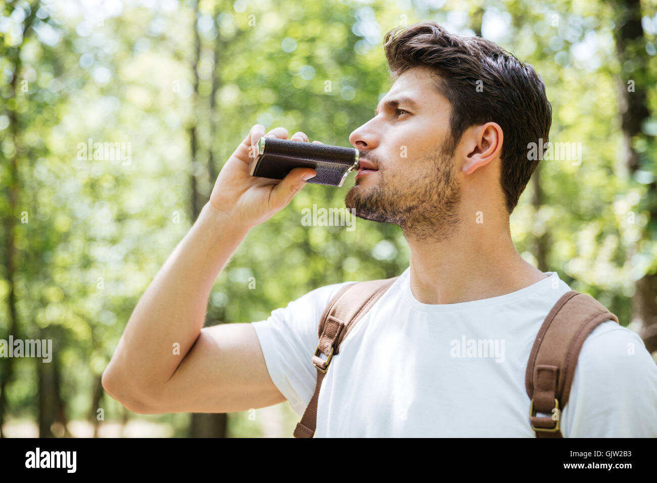 Handsome young man with backpack standing and drinking from flask in forest - Stock Image