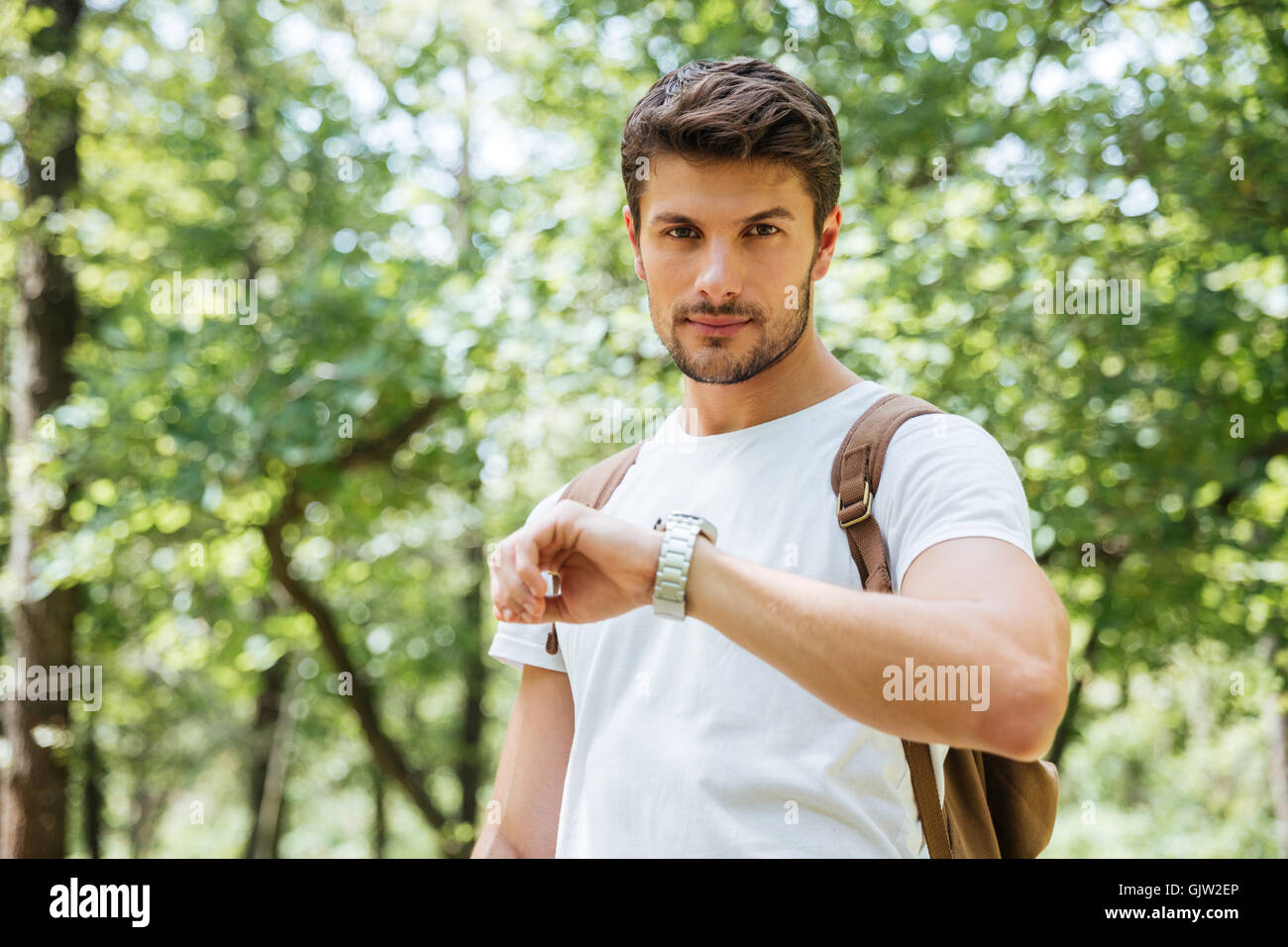Serious young man with backpack checking time and looking at watch in forest - Stock Image