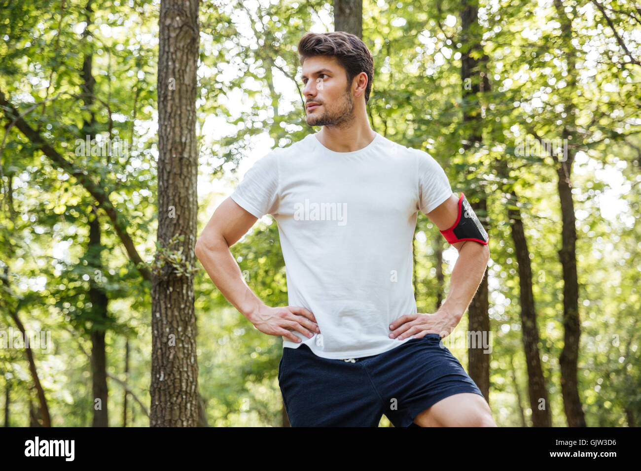 Portrait of attractive young man athlete with cell phone in handband standing in forest - Stock Image
