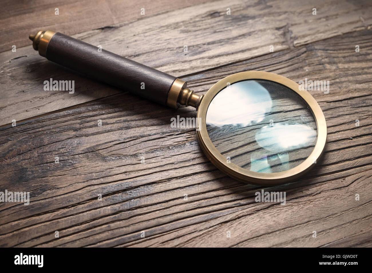 Retro style magnifying glass on a wooden tabe - Stock Image