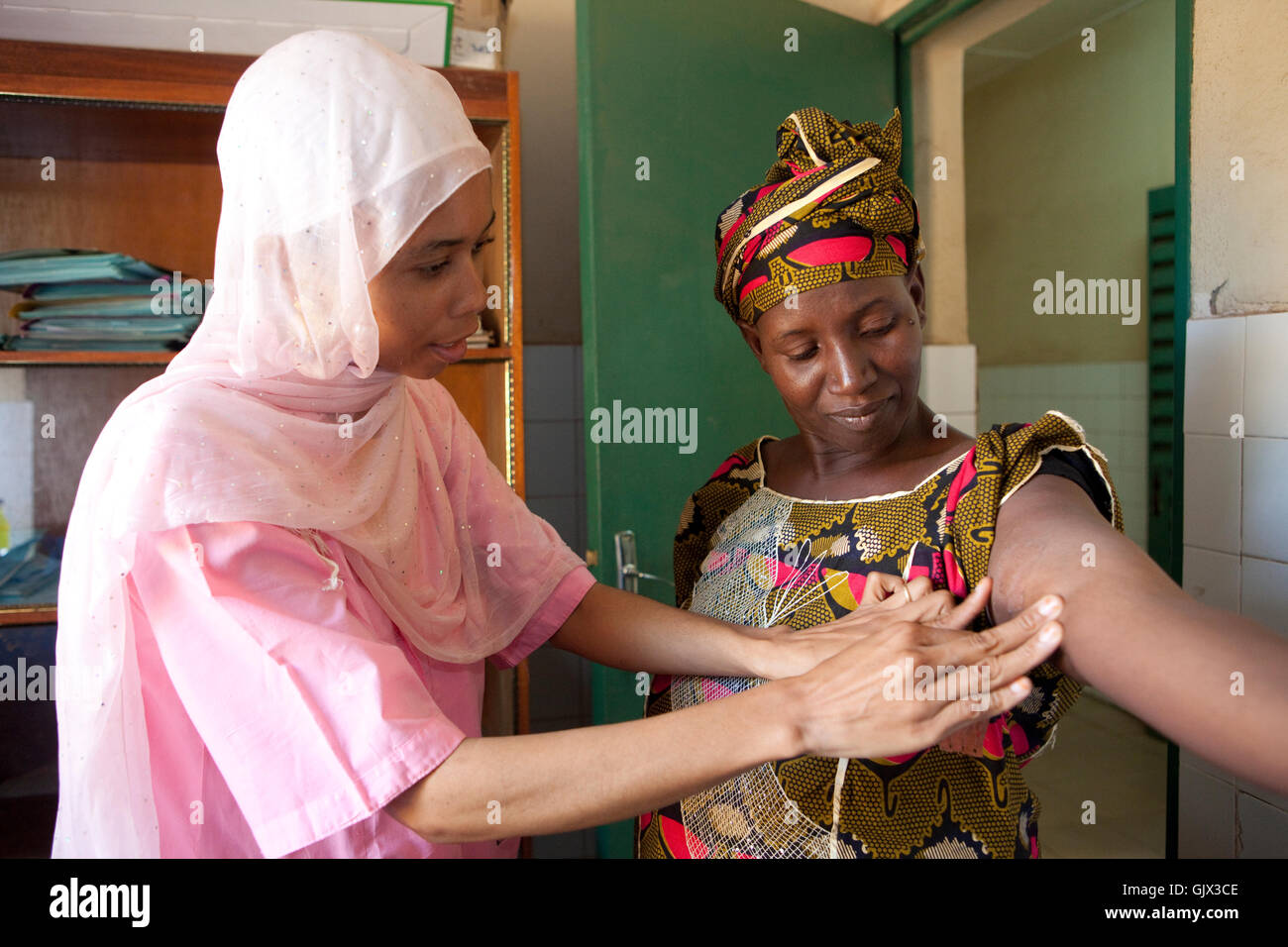 A midwife installs a contraceptive or hormonal implant in the arm of a woman in Bamako, Mali, West Africa. - Stock Image