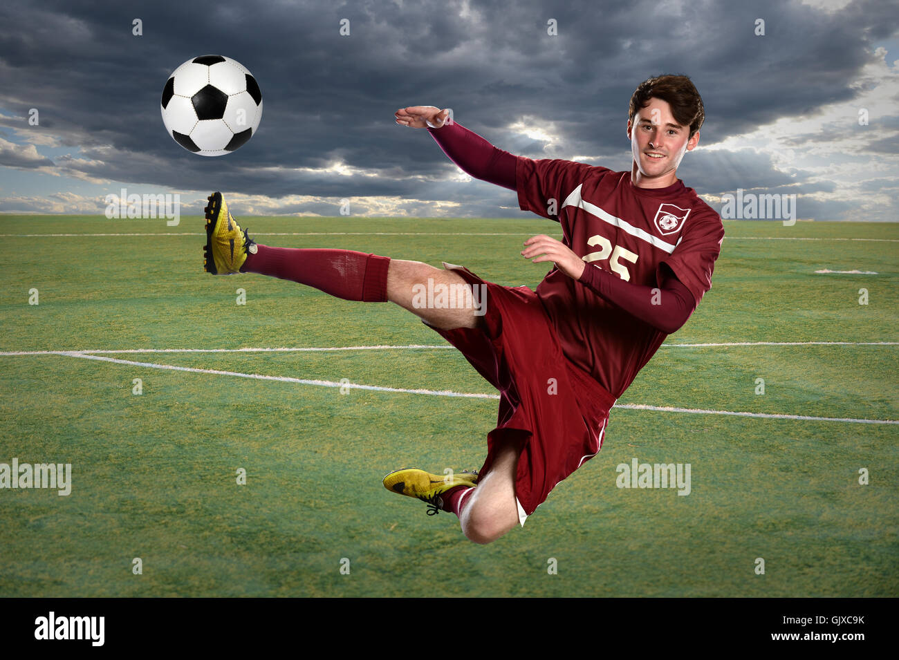 Young soccer player kicking ball while jumping - Stock Image