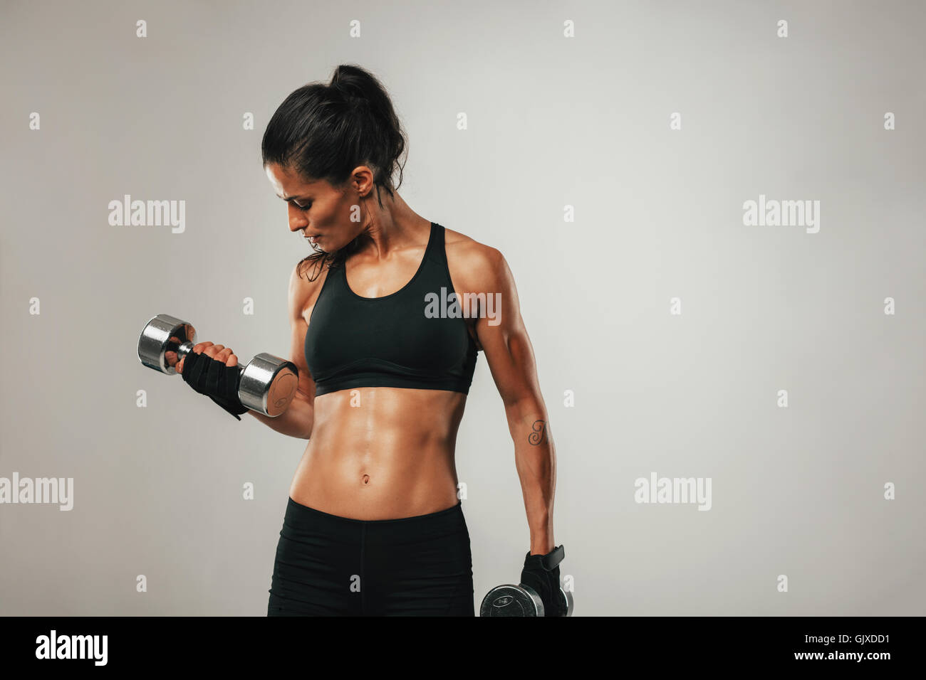Strong woman with tied up black hair and shorts curling dumbbell over gray background with copy space - Stock Image