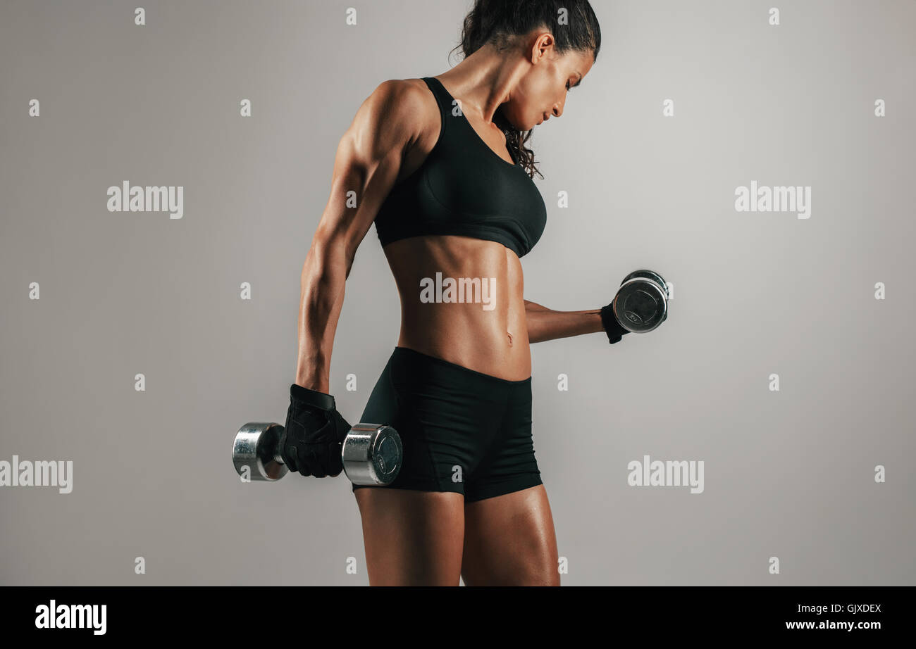 Single strong woman lifting chrome finish dumbbell weights over gray background with copy space - Stock Image