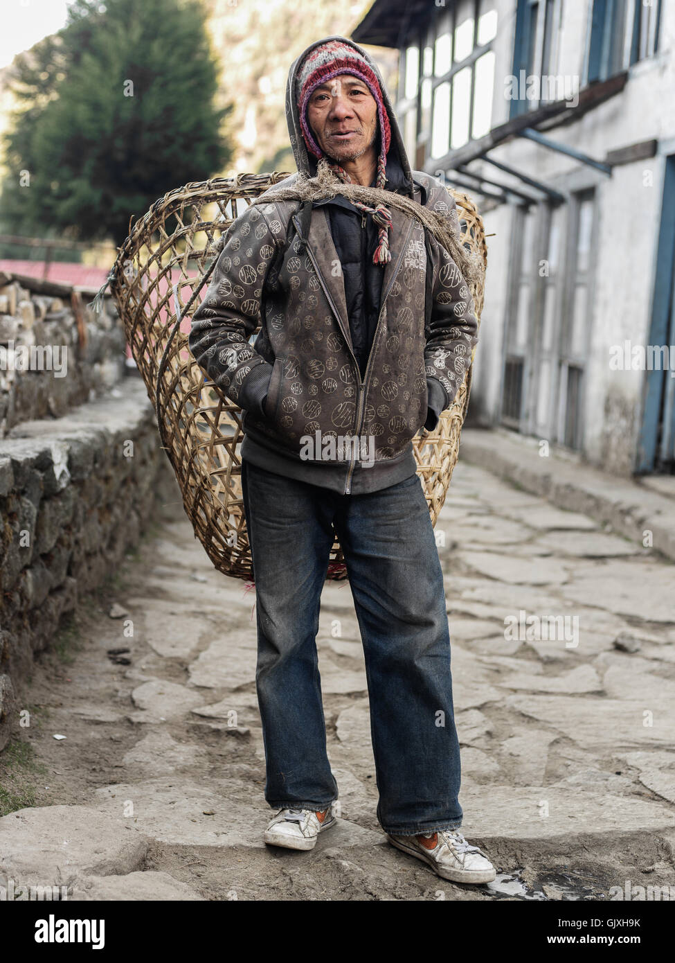 A Nepalese man carries his product in a basket backpack near Phakding, Nepal - Stock Image