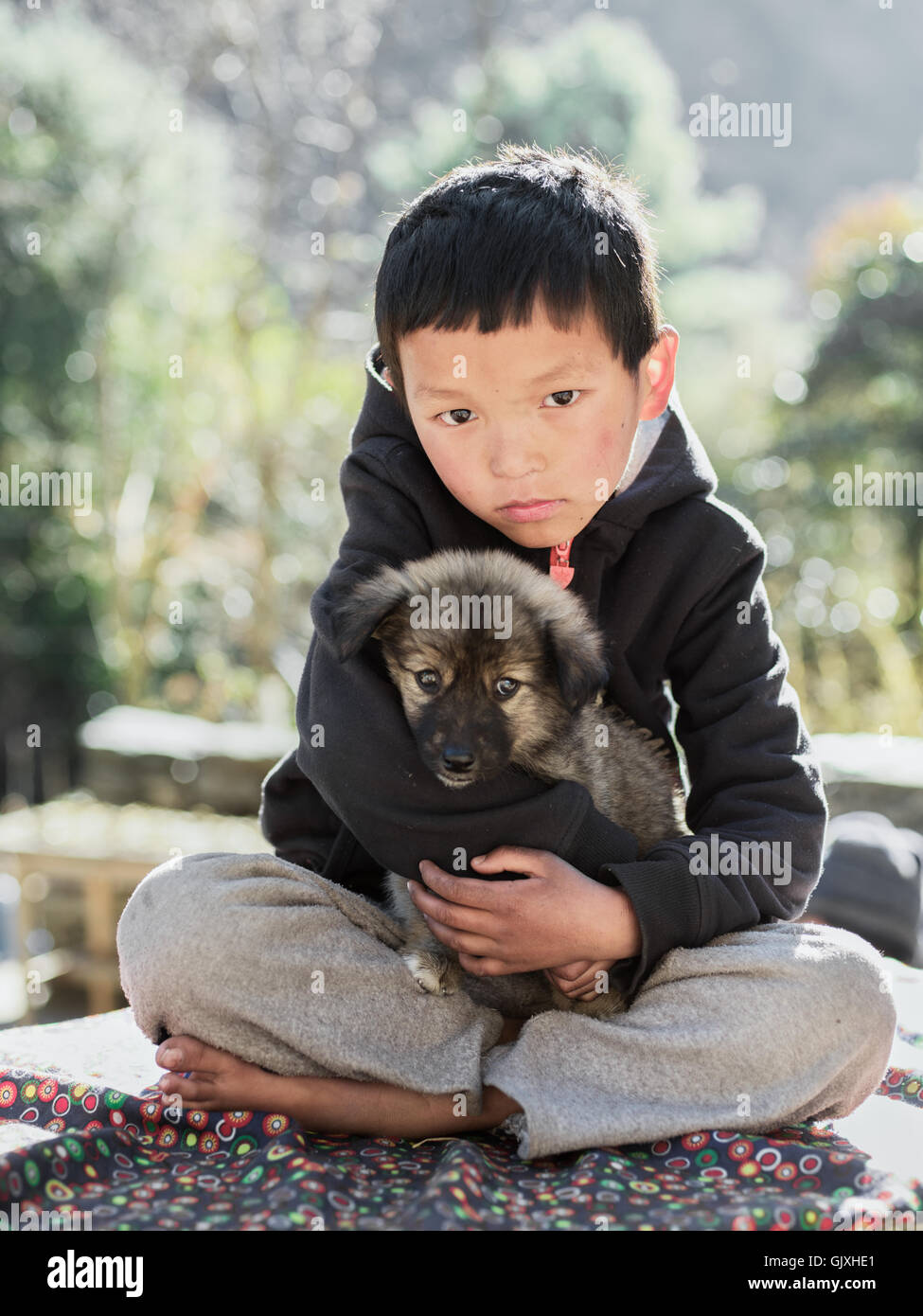 A Nepalese boy with his mountain puppy in Phakding, Nepal - Stock Image