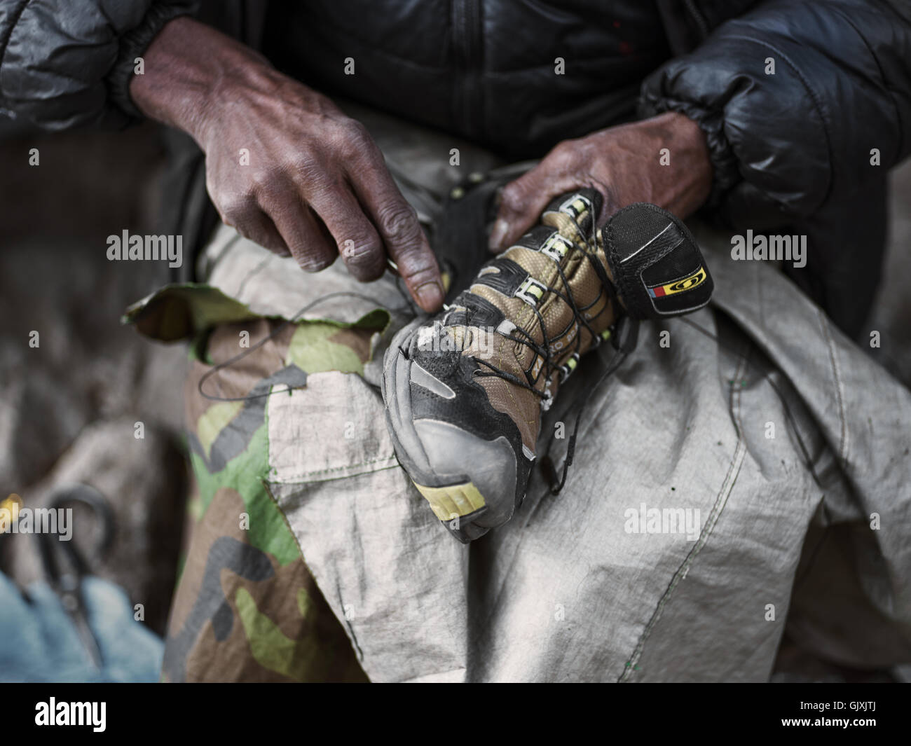 A Nepalese man repairs shoes in Namche, Nepal - Stock Image