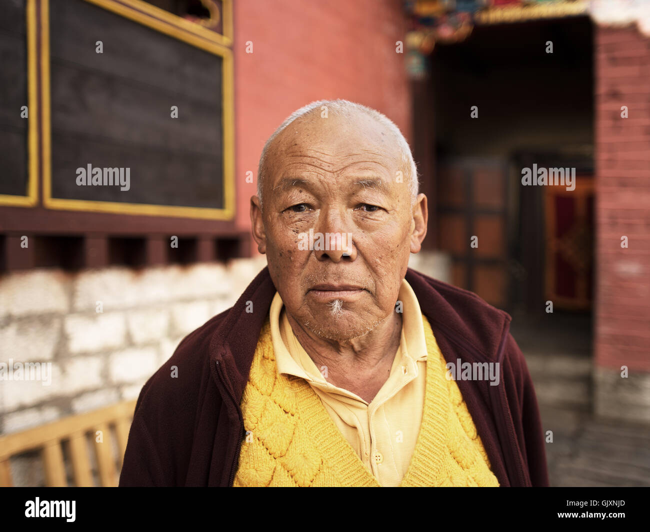 An old monk outside Tengboche Monastery in Nepal's Everest Base Camp - Stock Image