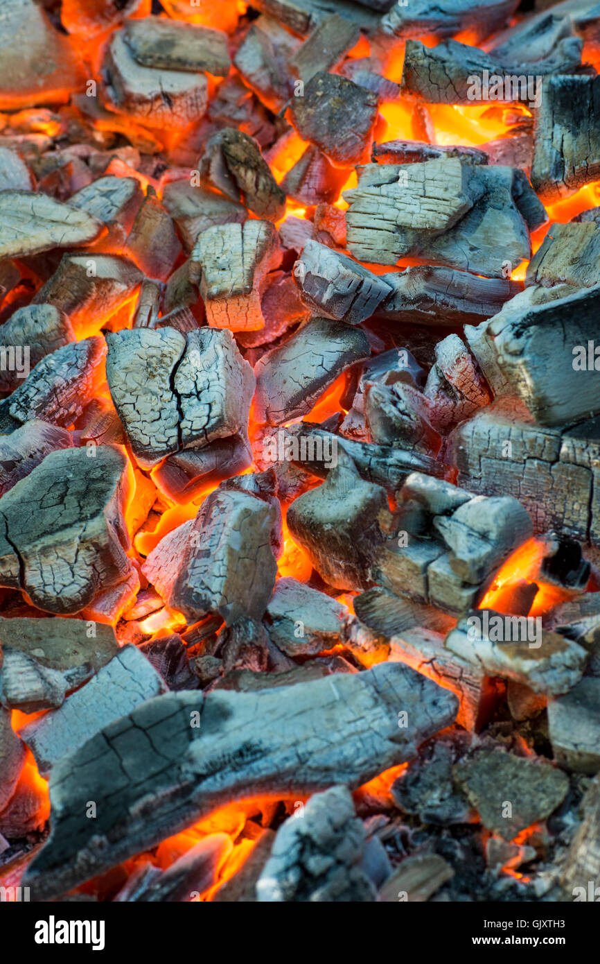 Burning coal. Glowing embers smoldering in the fireplace - Stock Image