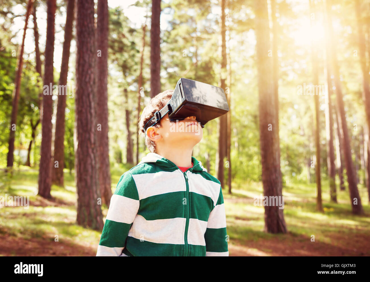 Child standing in the forest in virtual reality glasses - Stock Image
