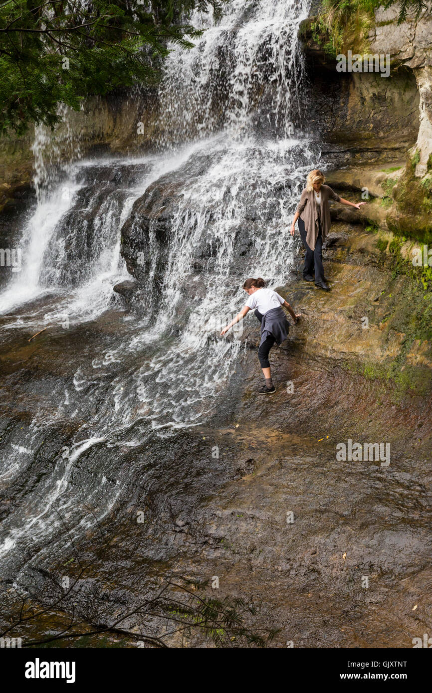 Sundell, Michigan - Tourists with perhaps more bravery than sense climb over wet rocks adjacent to Laughing Whitefish - Stock Image