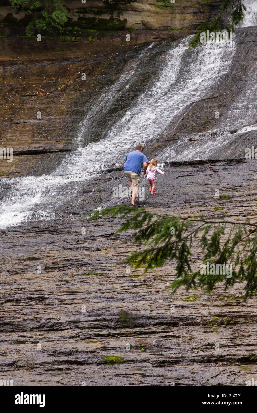 Sundell, Michigan - A man climbs with a small child over wet rocks adjacent to Laughing Whitefish Falls. - Stock Image