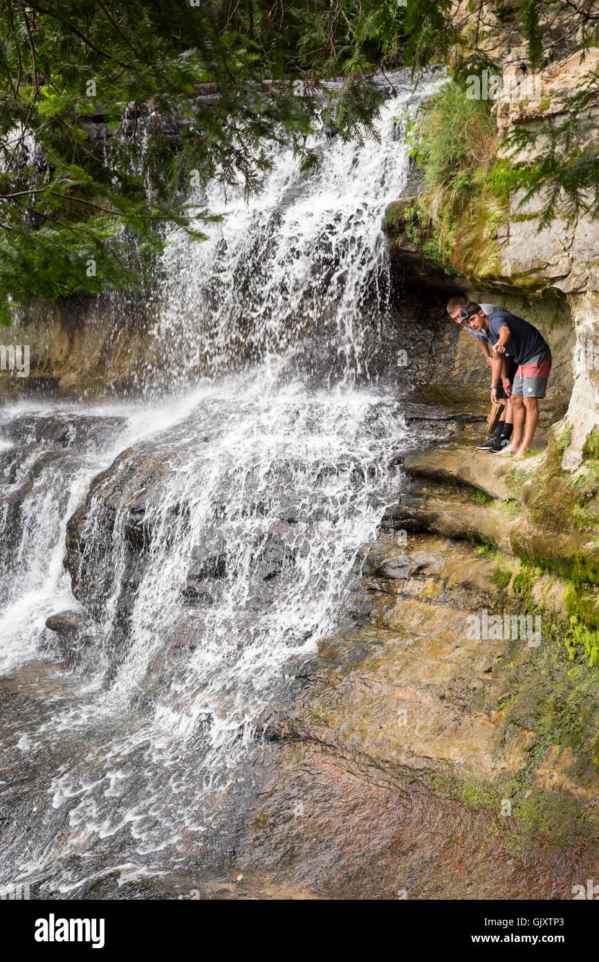Sundell, Michigan - Tourists climb behind Laughing Whitefish Falls, which drops 100 feet over a limestone escarpment. - Stock Image