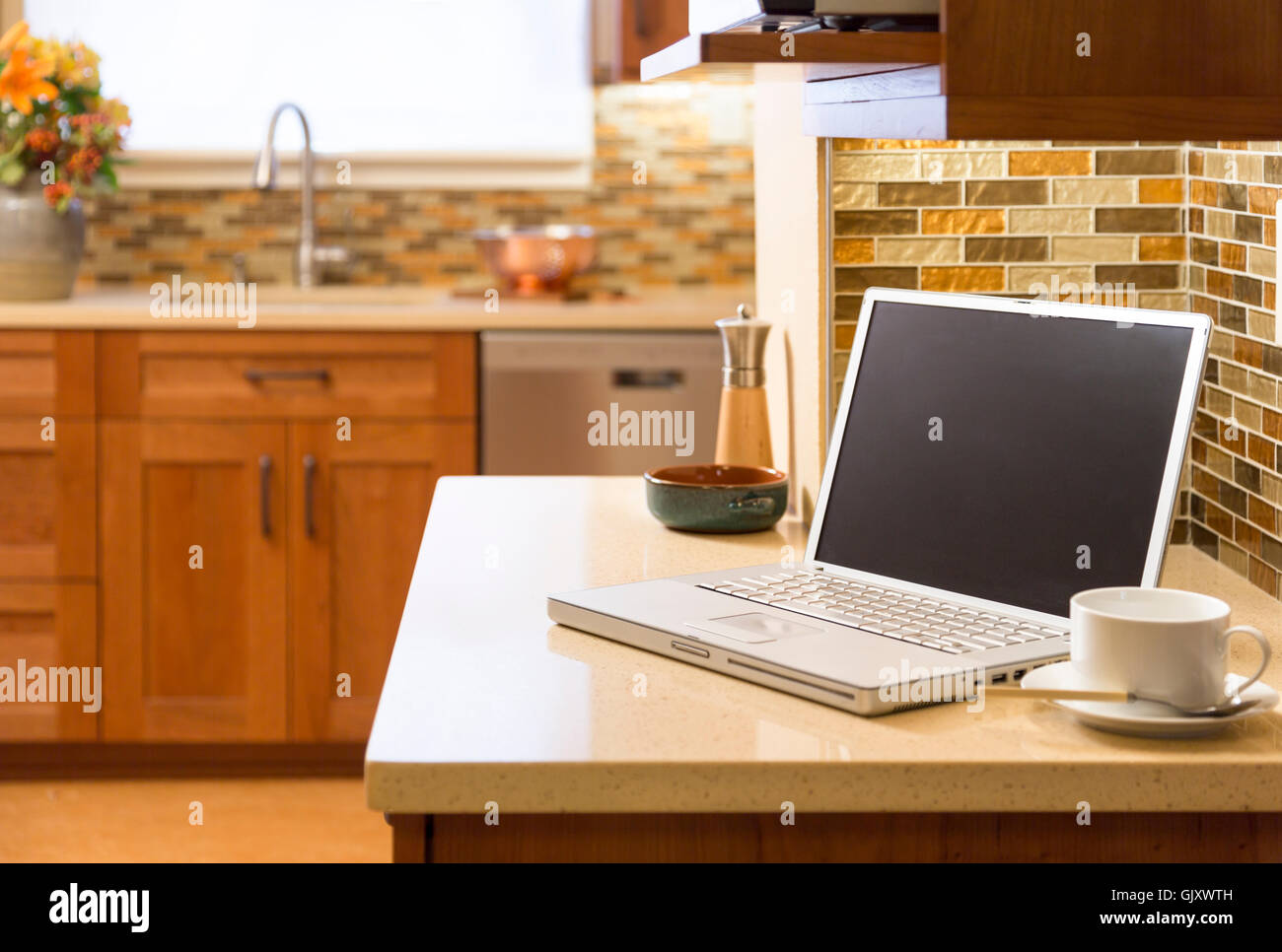 Laptop computer wireless wifi technology in contemporary upscale home kitchen interior. Working from home office. - Stock Image