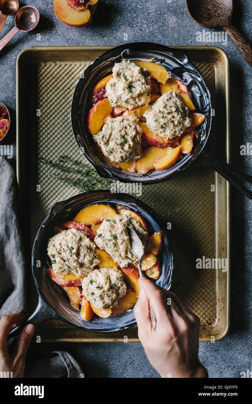 A woman is placing the last biscuit on top of peaches. - Stock Image