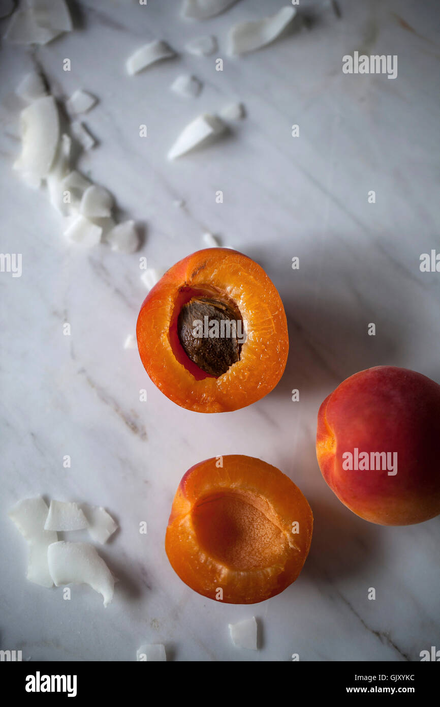 Fresh apricots and coconut flakes on white marble table - Stock Image
