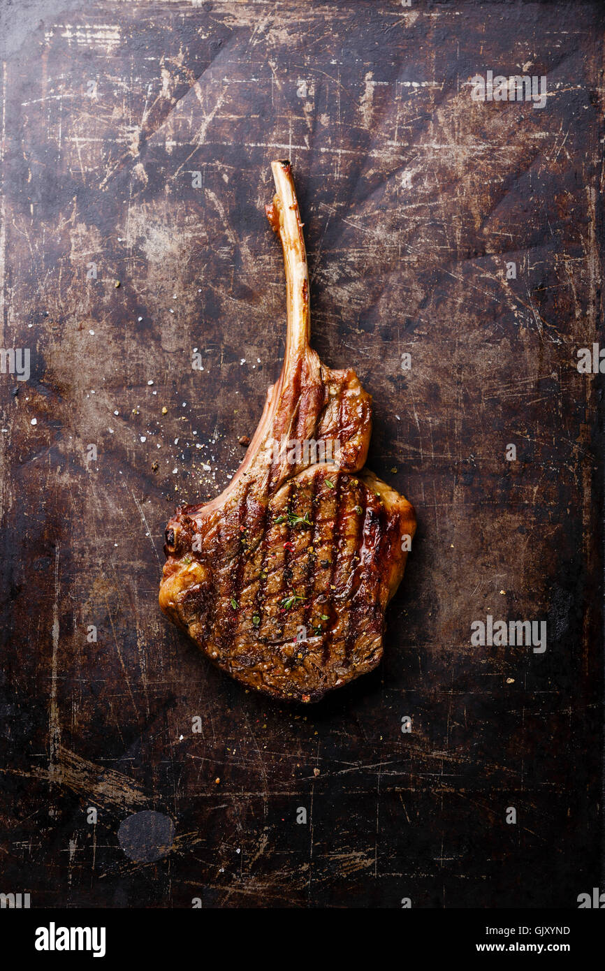 Grilled beef barbecue Veal rib on dark metal baking sheet background - Stock Image
