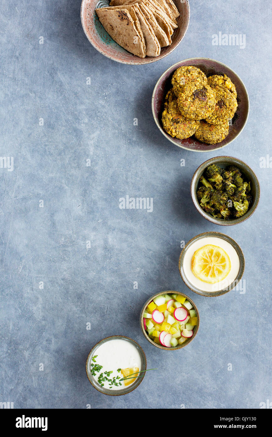 Ceramic bowls with charred broccoli falafel, charred lemon tahini, charred lemon tzatziki, charred broccoli, veggies - Stock Image