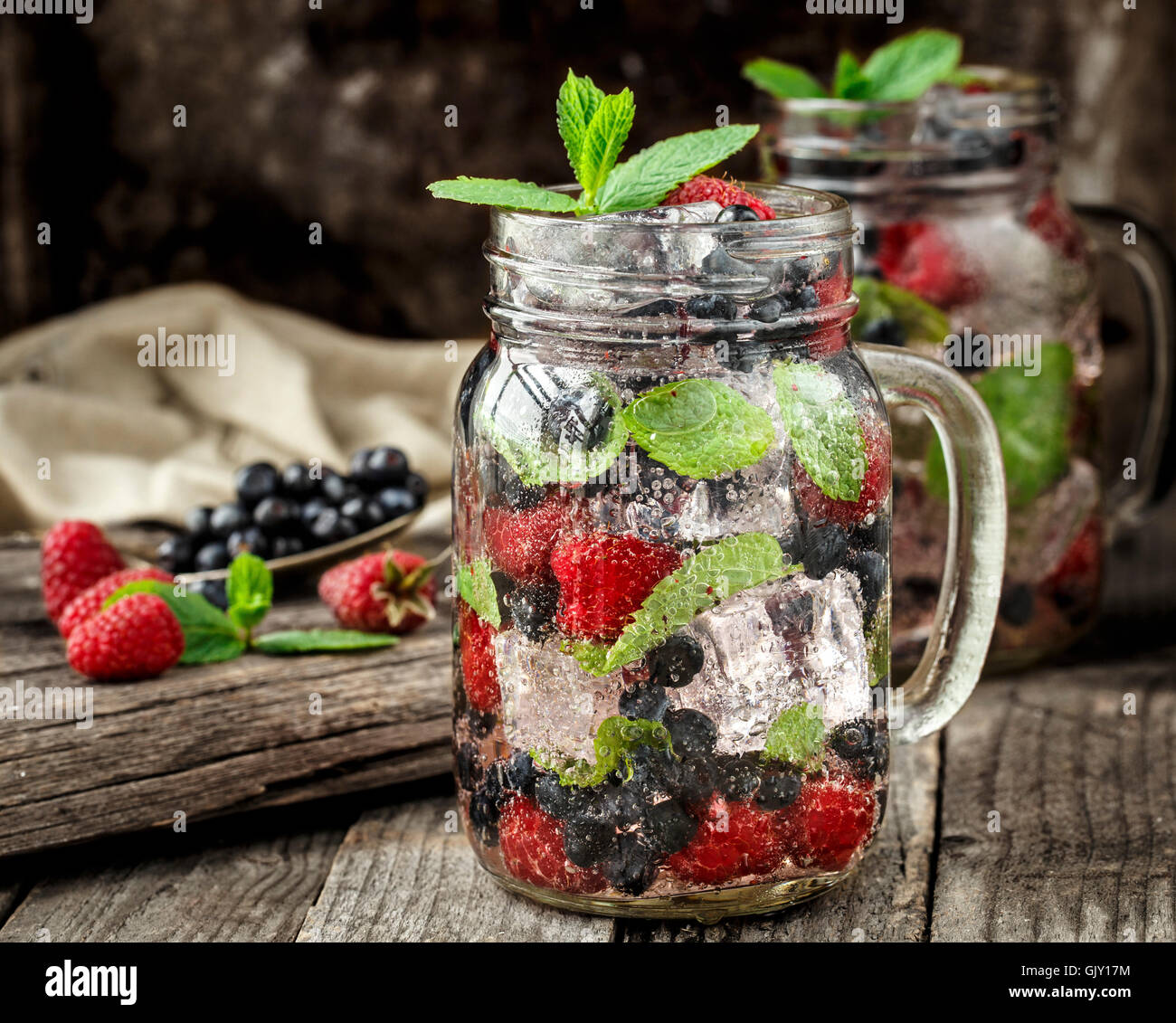 Detox drink with fresh berries, mint and ice in glass jars on wooden background - Stock Image