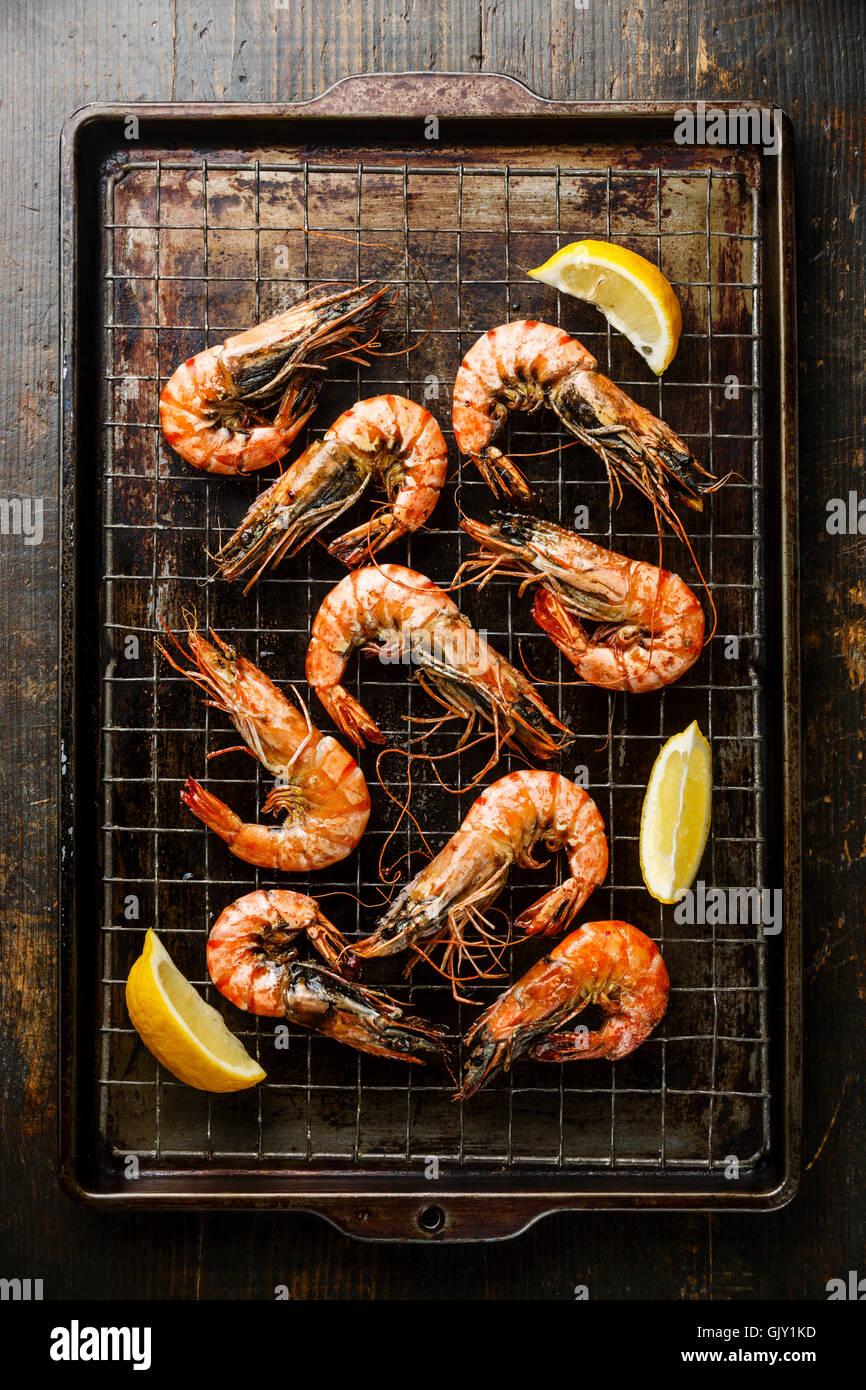 Tiger prawns roasted on metal baking sheet and lemon - Stock Image