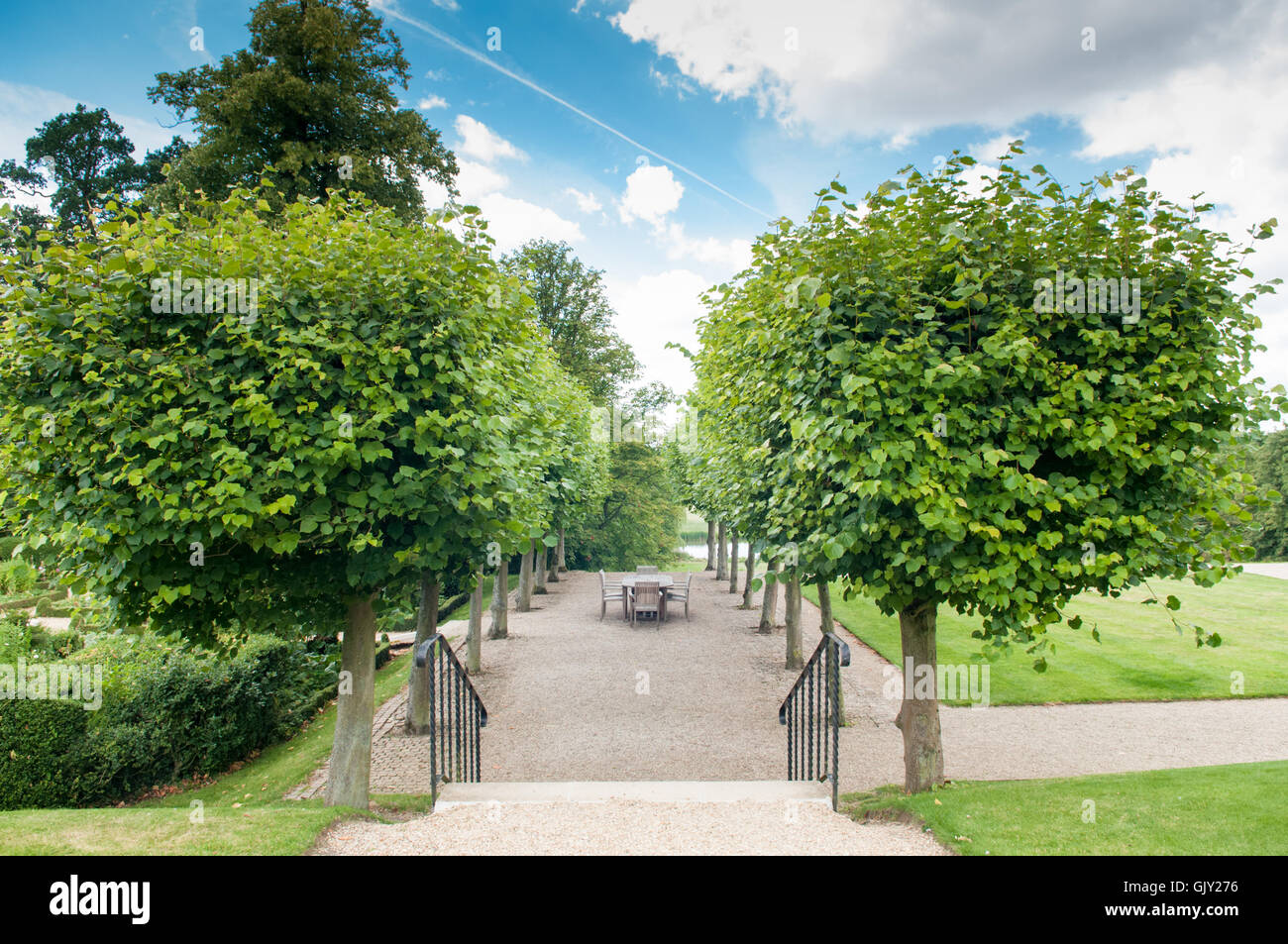 Formal garden entrance with shaped hedges and trees - Stock Image