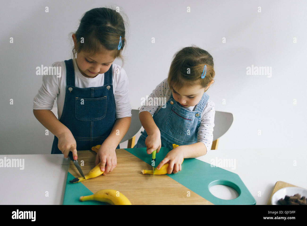 Two little girls chopping banana on the wooden board - Stock Image