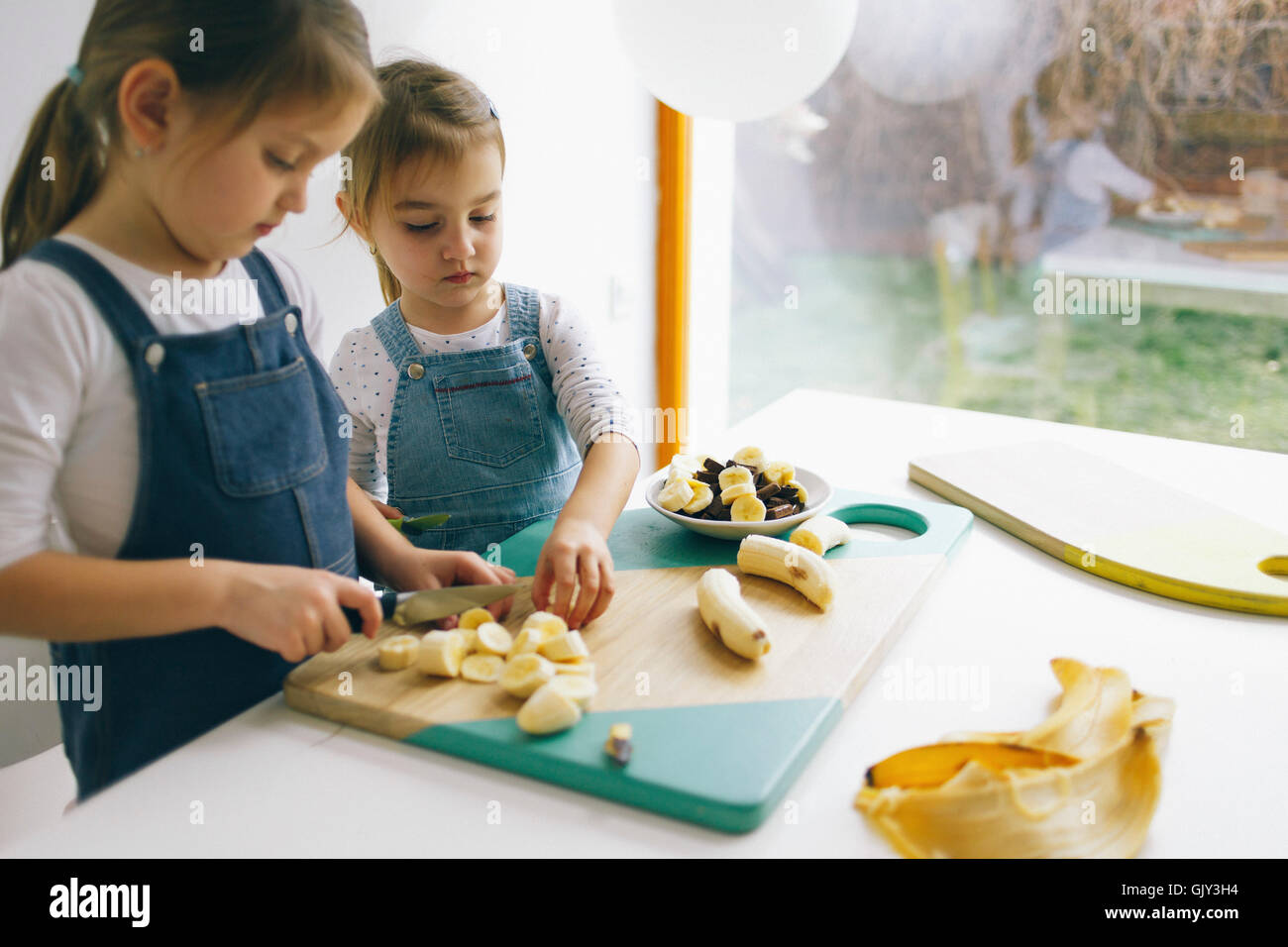 Two little girls chopping banana on the wooden board on the wooden board - Stock Image