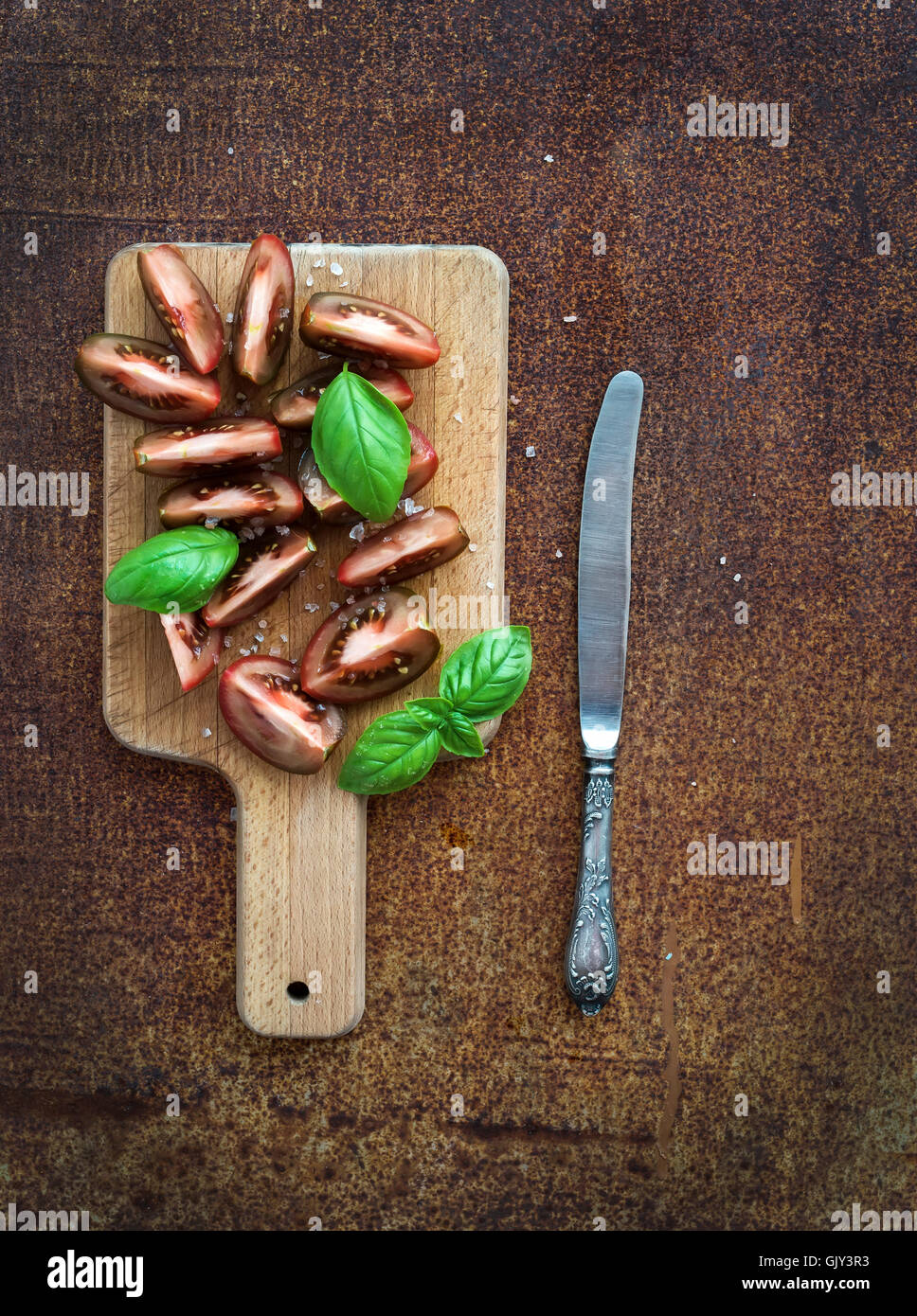 Fresh tomato slices with salt and basil leaves on wooden chopping board over grunge metal rusty background, top - Stock Image