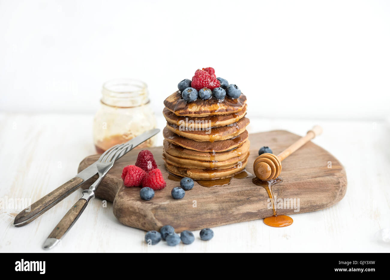 Homemade pancakes with fresh garden berries, honey on wooden board over white painted wooden background, selective - Stock Image