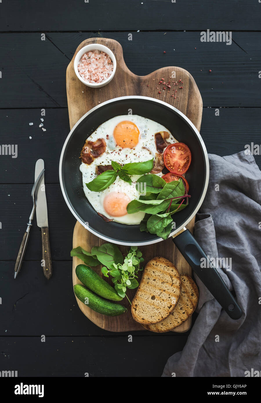 Pan of fried eggs, bacon, cherry tomatoes and fresh herbs with bread on wooden board over dark wooden background, - Stock Image
