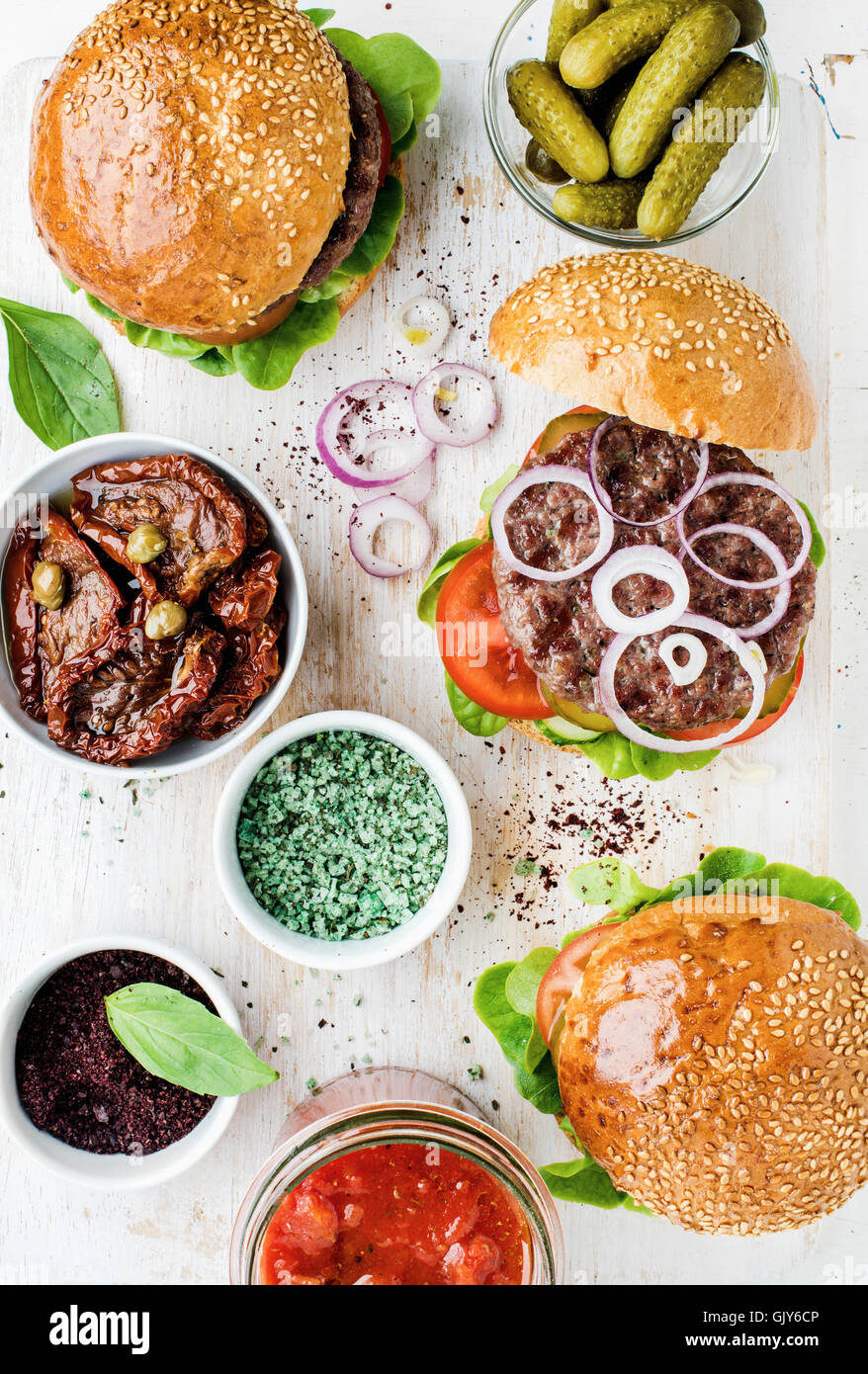 Homemade beef burgers with onion, pickles, fresh vegetables, spices, sun-dried tomatoes and tomato sauce on serving - Stock Image