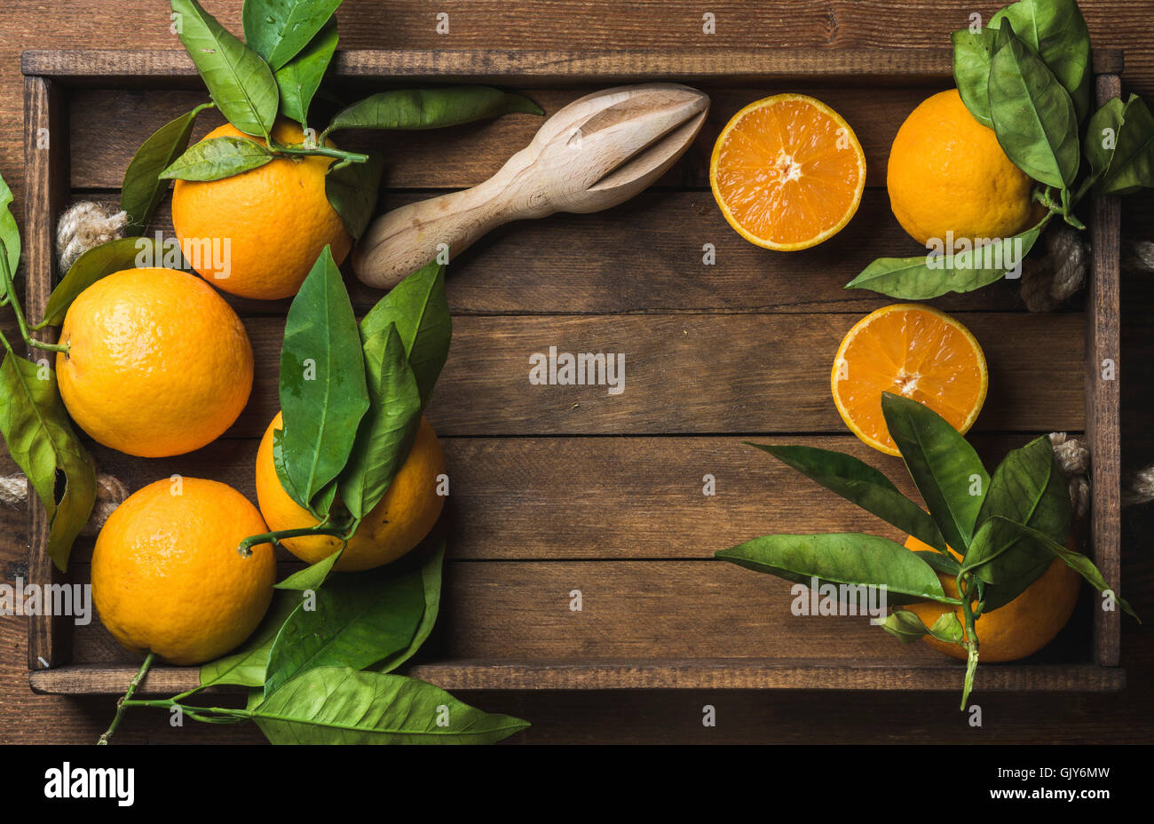 Fresh oranges with leaves in dark wooden tray over wooden background, top view, copy space, horizontal composition - Stock Image