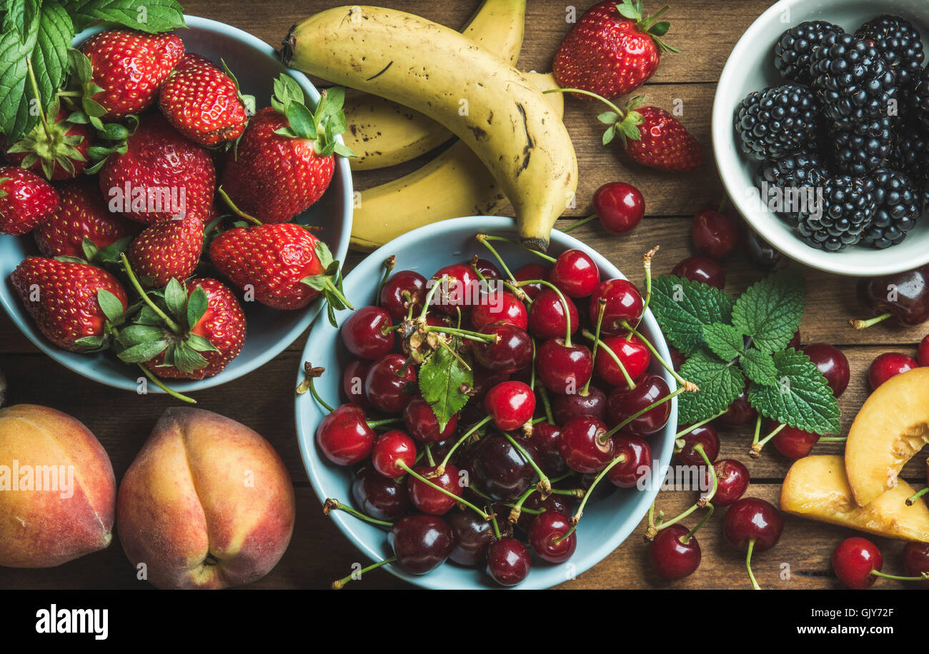 Summer fresh fruit and berry variety over wooden backdrop, top view, horizontal composition - Stock Image