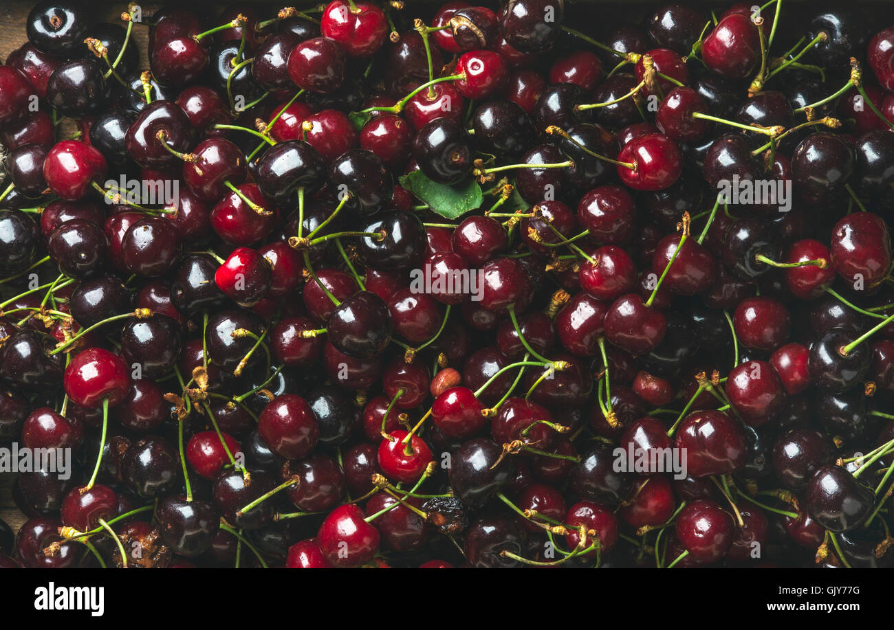 Background of dark red sweet cherries over wooden backdrop. Top view, horizontal composition Stock Photo