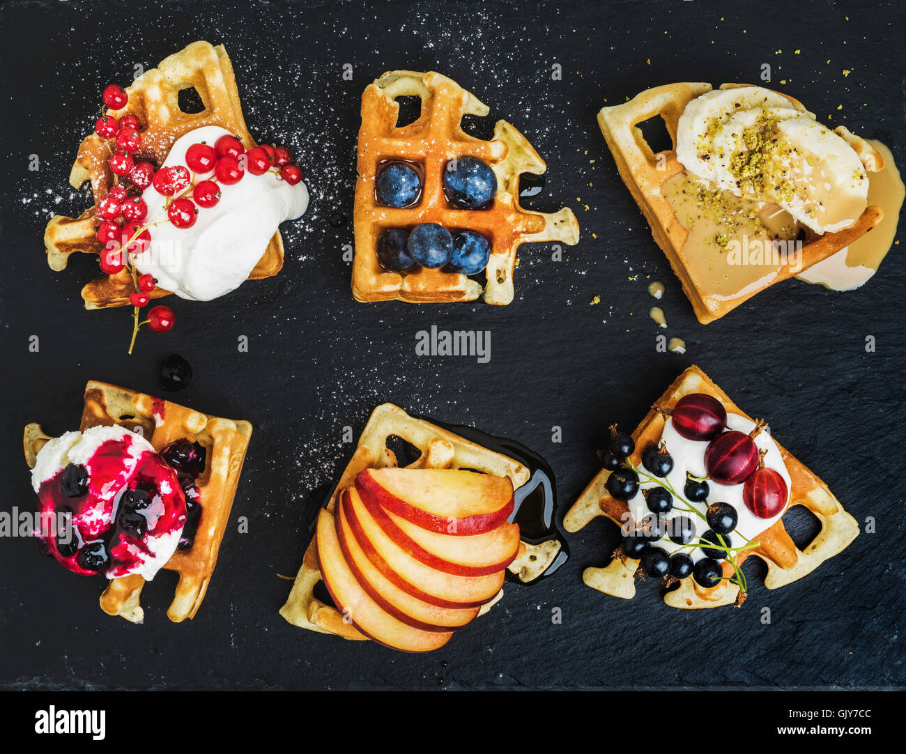 Warm belgian homemade waffles with fresh garden berries, fruit and ice cream on dark slate stone background, top - Stock Image