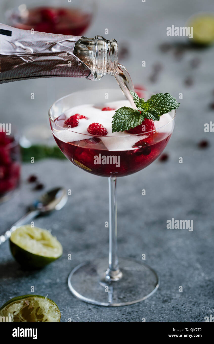 A glass of Raspberry and Pomegranate Champagne Cocktail is being topped of with champagne - Stock Image