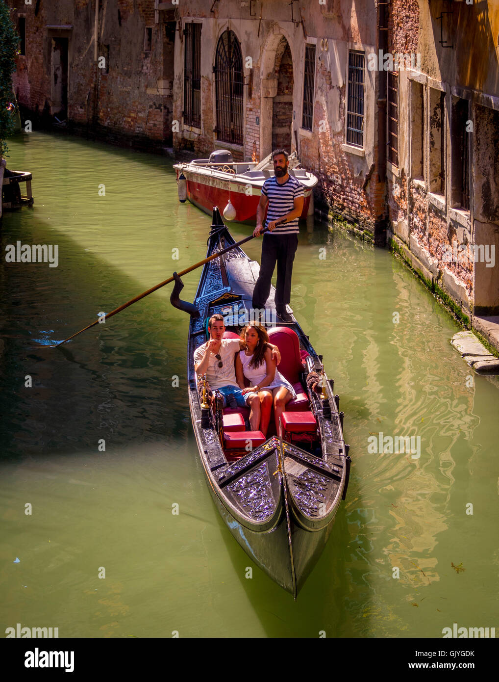 Gondolier wearing traditional striped top steering his gondola along a narrow canal in Venice, Italy. - Stock Image