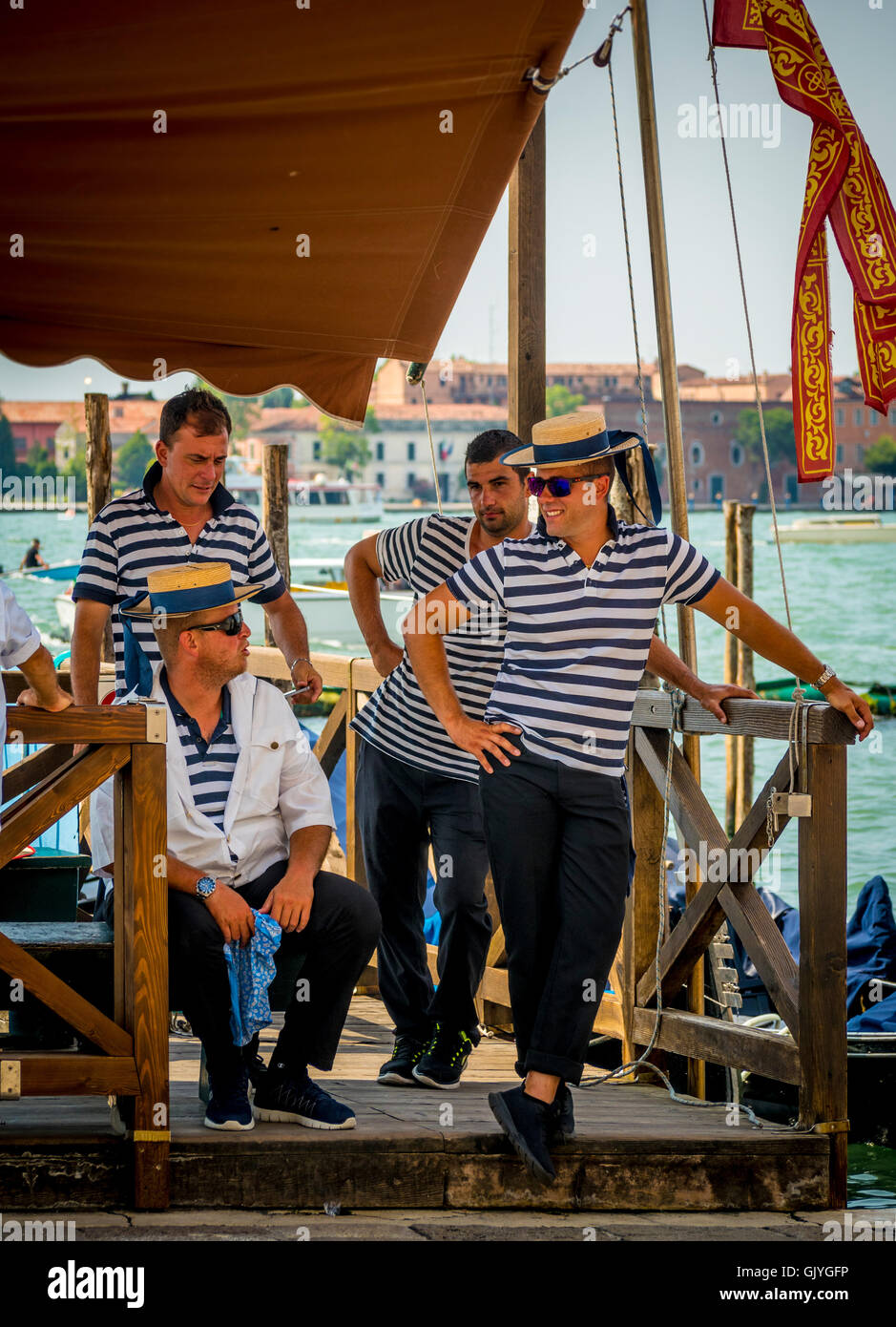 4 male gondoliers wearing traditional striped tops and straw boater hats, waiting for passengers. Venice, Italy. - Stock Image