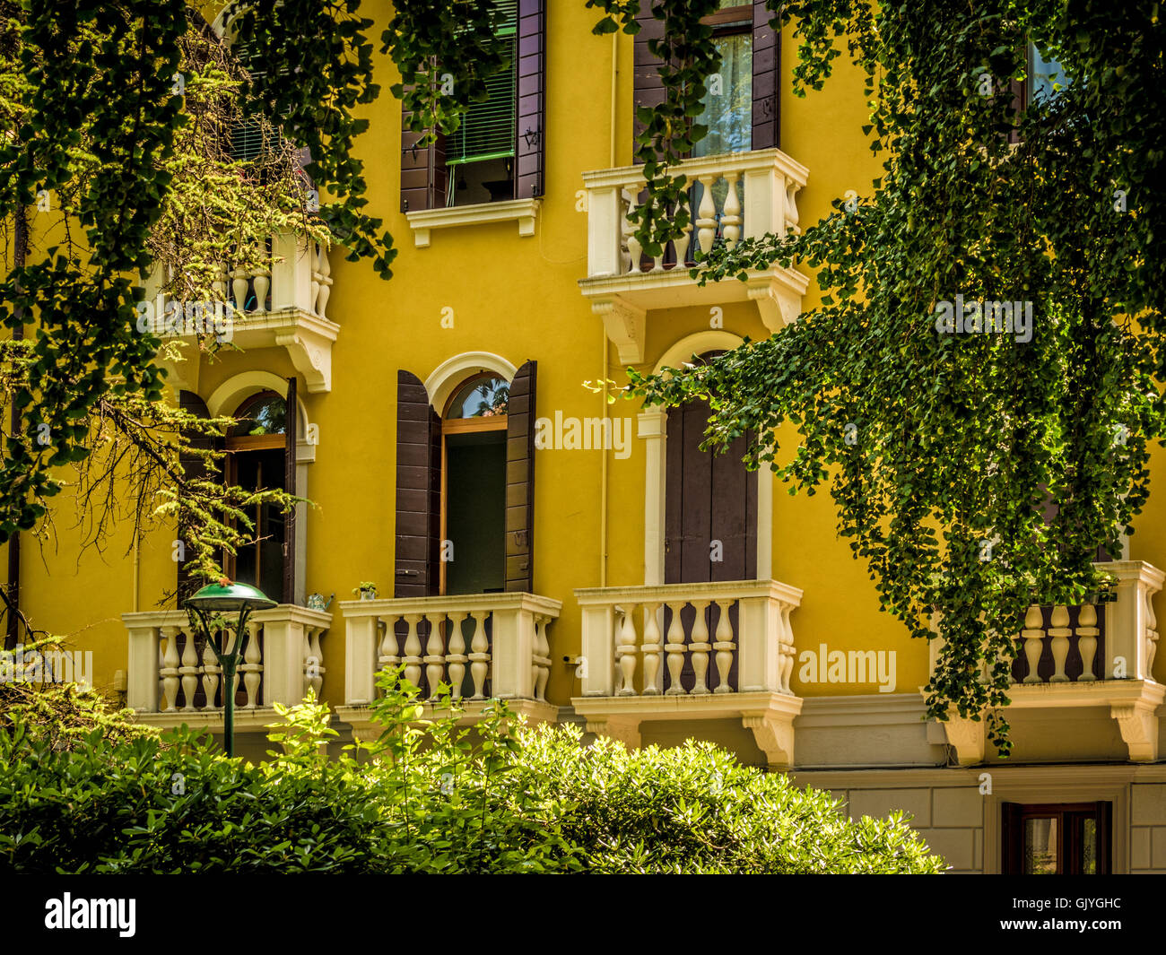 Traditional yellow rendered building with shutters and venetian blinds at the arched windows. Venice, Italy. - Stock Image
